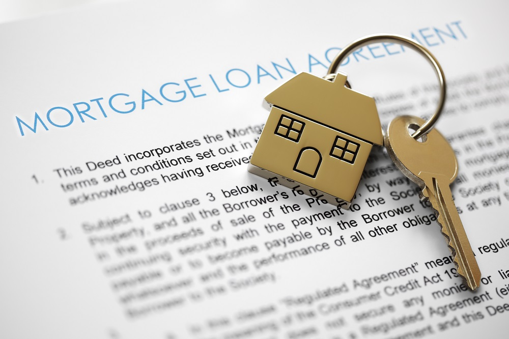 home keychain and key on mortgage loan agreement paperwork