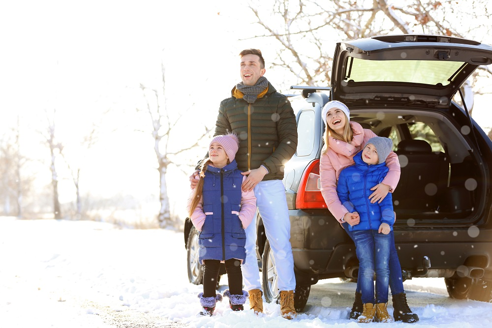 family outside of car in the snow