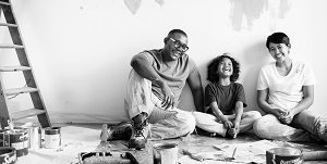 father son and mother sitting on the floor taking a break from painting walls inside their home
