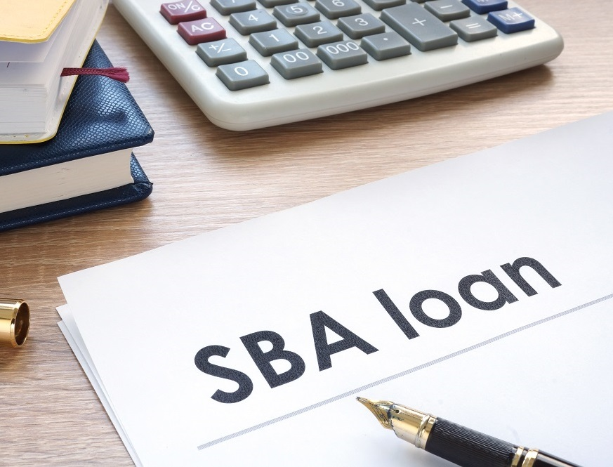 SBA loan documents, calculator and pen on desk