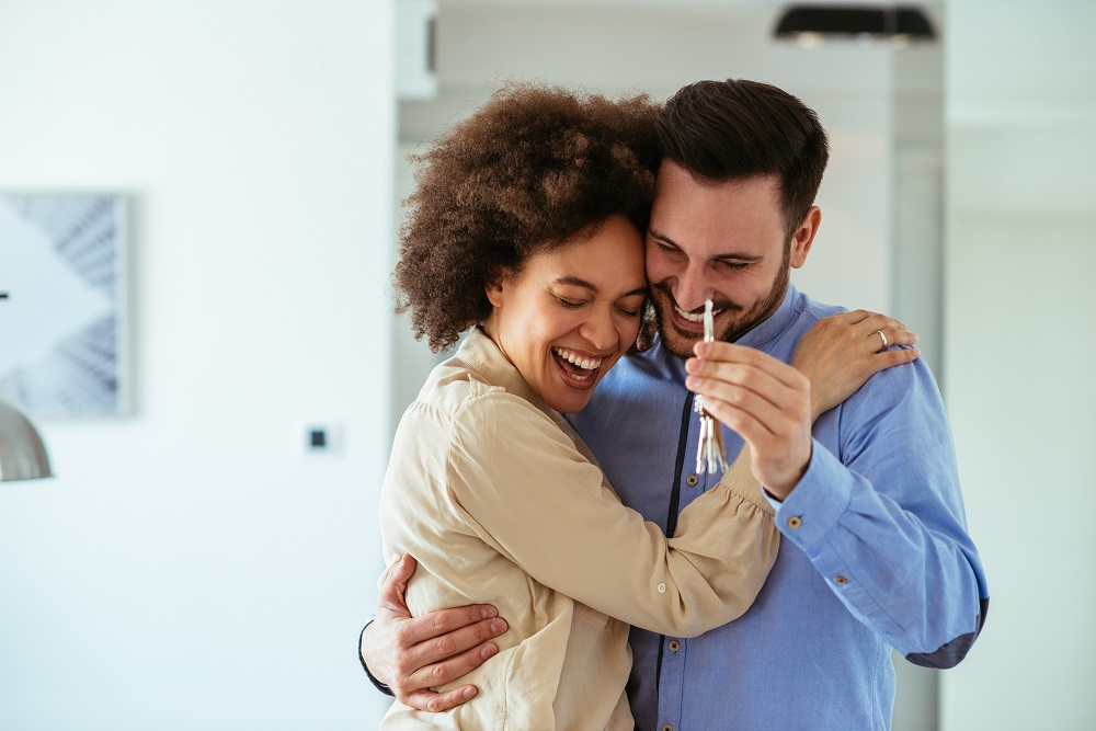 young homebuyers hugging and smiling, holding the key to their first home