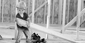 little boy wearing a hardhat doing construction work in a house