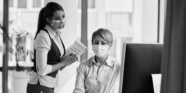 Two female business owners with face masks on looking at a computer screen