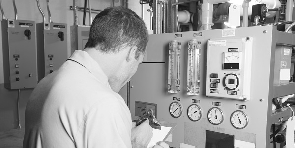 heating technician checking commercial heating controls at a business