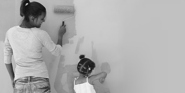 Mother and daughter painting a wall together as they renovate their home