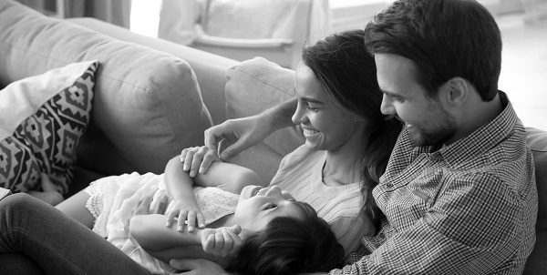 young couple and their daughter laughing and cuddling on their couch at home