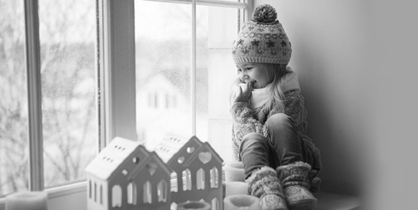 little girl in winter hat and slippers and sweater sitting near a drafty window on a winter day