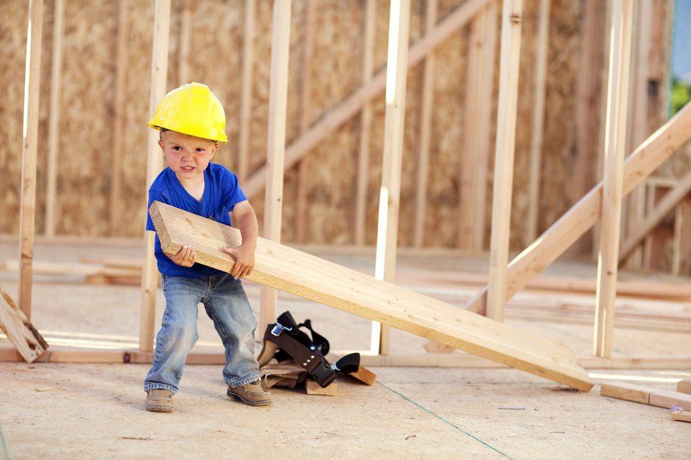 little boy wearing hardhat holding a piece of plywood