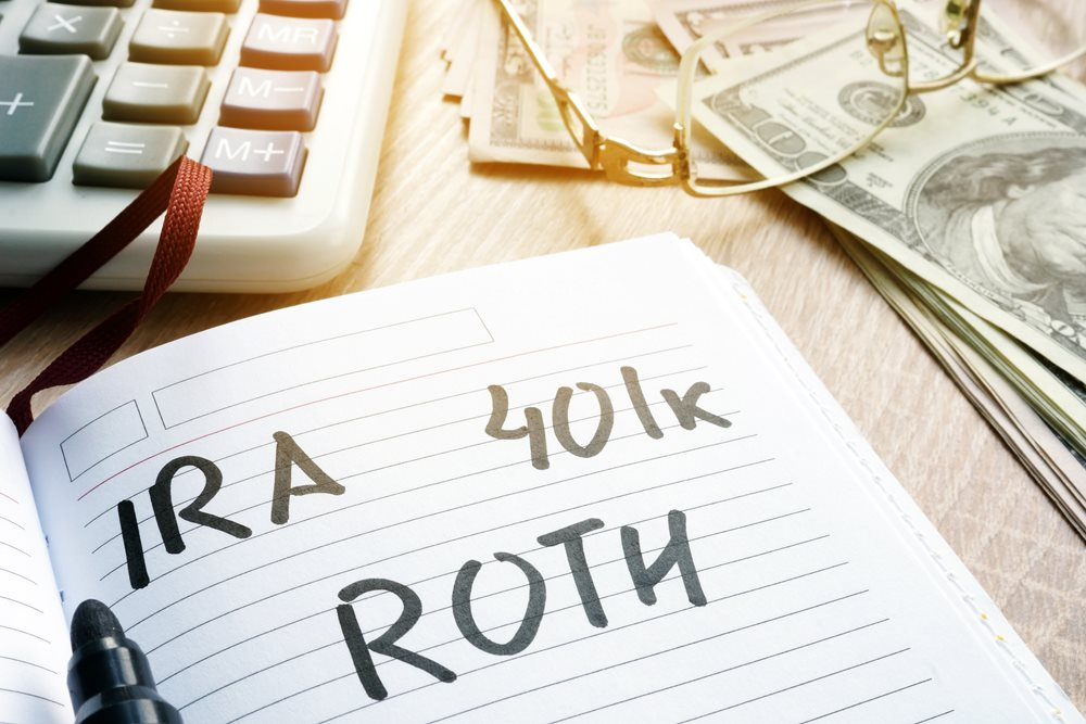 IRA, 401k, and Roth written on a sheet of note paper, surrounded by money and a calculator