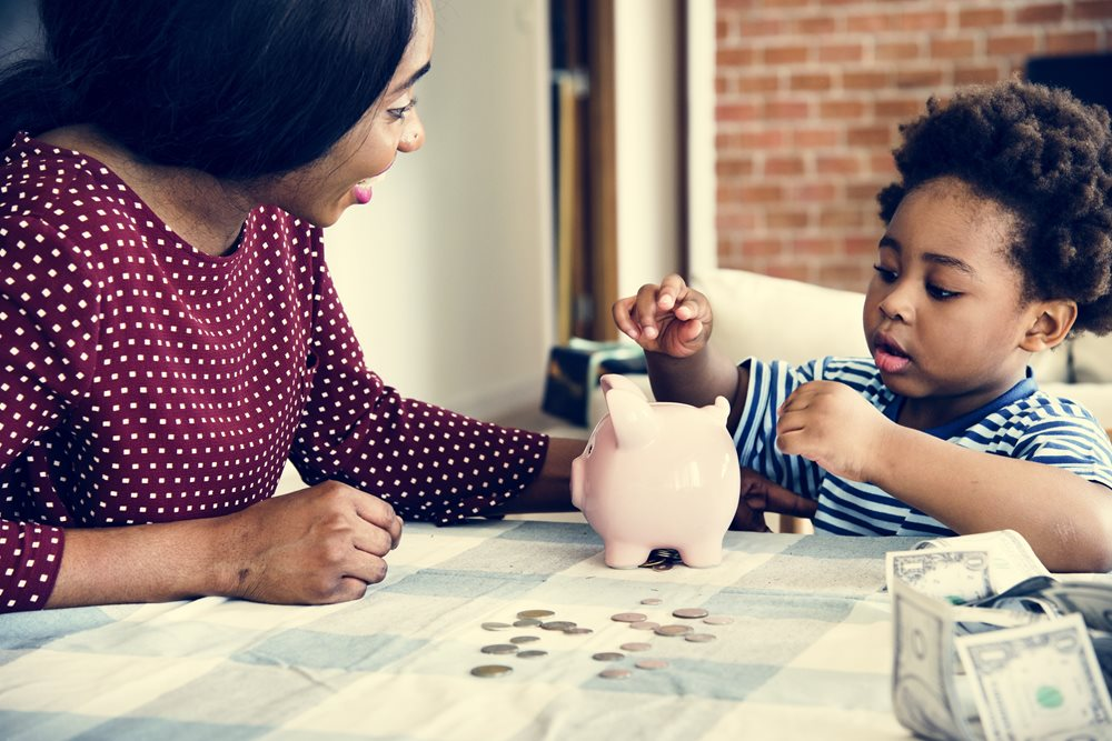 mother showing her toddler son how to count change with coins and a piggy bank